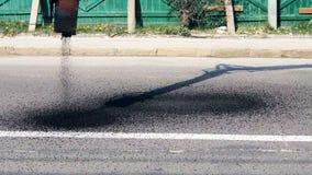 Automatische levering van heet asfalt voor reparatie van kuilen op de weg stock videobeelden