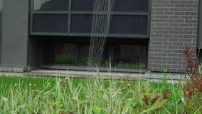 Automatische sprenkelinstallatie die het gazon op een achtergrond van groen gras water geven stock footage