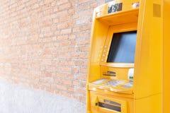 Automatische Tellermachine ATM De gele contant gelddoos wordt gevestigd naast de bakstenen muur Om alle diensten te gebruiken aan Royalty-vrije Stock Afbeelding