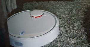 Automatiseert de robot stofzuiger op tapijtvloer, Slimme robotachtig draadloze schoonmakende technologiemachine in woonkamer stock footage