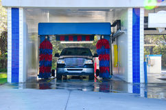 Automatiserad bilwash med ett soapy åker lastbil Arkivbild