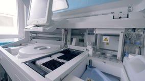 Automatiserad maskin som arbetar i ett laboratoriumrum som analyserar stock video