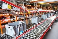 Automatiserat lager Askar med reservdelar som är rörande på transportör Royaltyfria Bilder