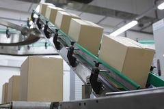 Automatisering - Kartondozen op transportband stock afbeelding