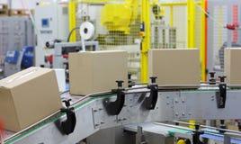 Automatisering - Kartondozen op transportband in fabriek stock fotografie