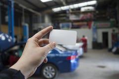Automatisk arbetarhåll ett tomt besökkort Fotografering för Bildbyråer