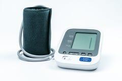 Automatisk bärbar blodtryckmaskin med armmanschetten på vit, studioskott Fotografering för Bildbyråer