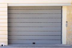 Automatisk grå garagedörr som stängs, med en klocka på dörren royaltyfri fotografi