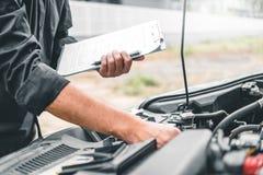 Automatisk mekaniker som arbetar i för Maintenance för skrivplatta för garageteknikerinnehav och kontrollmekanikerkontroll bil royaltyfri fotografi
