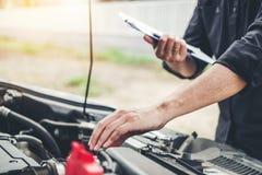 Automatisk mekaniker som arbetar i för Maintenance för skrivplatta för garageteknikerinnehav och kontrollmekanikerkontroll bil arkivbilder
