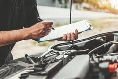 Automatisk mekaniker som arbetar i f?r Maintenance f?r skrivplatta f?r garageteknikerinnehav och kontrollmekanikerkontroll bil royaltyfria bilder