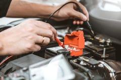 Automatisk mekaniker som arbetar i garageteknikeren Hands av bilmekanikern som arbetar batteri f?r bil i f?r service och underh?l arkivfoto
