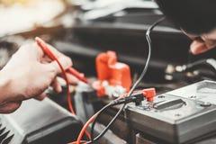 Automatisk mekaniker som arbetar i garageteknikeren Hands av bilmekanikern som arbetar batteri f?r bil i f?r service och underh?l royaltyfria bilder