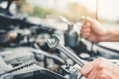 Automatisk mekaniker som arbetar i garageteknikeren Hands av bilmekanikern som arbetar kontroll i f?r service och underh?llsf?r b arkivbild