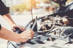 Automatisk mekaniker som arbetar i garageteknikeren Hands av bilmekanikern som arbetar kontroll i f?r service och underh?llsf?r b royaltyfri foto