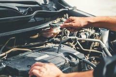 Automatisk mekaniker som arbetar i garageteknikeren Hands av bilmekanikern som arbetar kontroll i f?r service och underh?llsf?r b arkivbilder