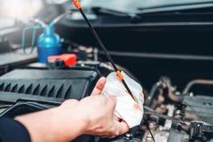 Automatisk mekaniker som arbetar i garageteknikeren Hands av den mekanikerOil Check mekanikern som arbetar i f?r automatisk repar fotografering för bildbyråer