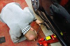 Automatisk mekaniker som ser under bilen för att installera stålar royaltyfria foton