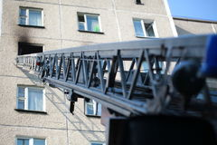 Automatisk stege av brandmotorn till ett brinnande hus royaltyfria foton