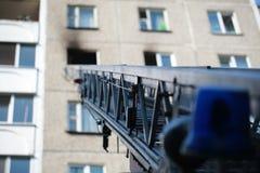 Automatisk stege av brandmotorn till ett brinnande hus royaltyfri foto