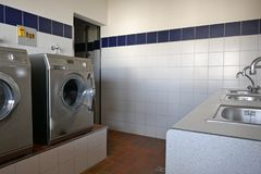 Automatisk tvättmaskiner och tabsin för rostfritt stålvaskiand ett modernt nytto- rum av en campingplats fotografering för bildbyråer