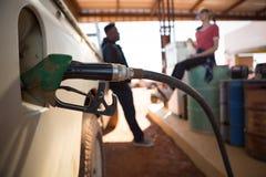 Automatiska dysor som fyller bensin in i bilbehållare fotografering för bildbyråer