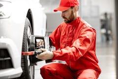 Automatiska mekaniker som gör hjuljustering på bilservicen arkivbilder