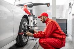 Automatiska mekaniker som gör hjuljustering på bilservicen arkivbild