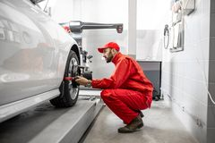Automatiska mekaniker som gör hjuljustering på bilservicen fotografering för bildbyråer