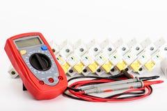 Automatiska strömkretssäkerhetsbrytare, digital multimeter Elektrisk utrustning, skydd och kontroll, vit bakgrund royaltyfria bilder