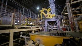 Automatización industrial Brazo robótico que monta los nuevos materiales de construcción en la banda transportadora almacen de video