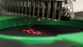 Automatyczna szwalna maszyna Robot szwalna maszyna automatyzuj?ca maszyna haftuje wz?r z czerwonymi niciami na czerni zbiory