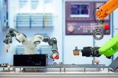 Automazione industriale di robotica che lavora tramite nastro trasportatore sulla fabbrica astuta immagine stock libera da diritti