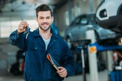 Automechanic holding car keys. And digital tablet at a repair shop stock photography