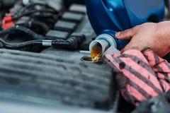 Automechanic som ändrar motorisk olja Royaltyfri Foto