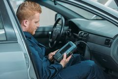 Automechanic using car diagnostic tool. Automechanic sitting in a car, using a car diagnostic tool Stock Images