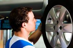 Automechaniker in änderndem Gummireifen der Werkstatt Stockbild