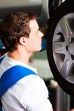 Automechaniker in änderndem Gummireifen der Werkstatt Stockbilder