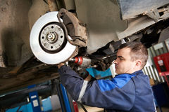 Automechaniker bei der Autosuspendierungsreparaturarbeit