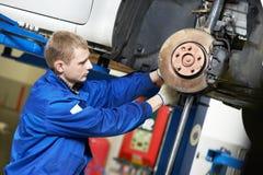 Automechaniker bei der Autosuspendierungsreparaturarbeit Lizenzfreies Stockfoto