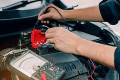 Automechaniker benutzt das Autobatteriemeter, um verschiedene Werte zu messen und ihn zu analysieren stockbild