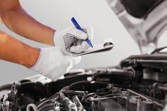Automechaniker, der Automotor an der Garage überprüft stockfoto