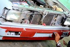 Automechaniker, der die Frontstoßstange eines Autos für das Malen vorbereitet Stockbilder