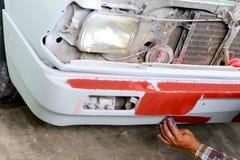 Automechaniker, der die Frontstoßstange eines Autos für das Malen vorbereitet Stockfotos