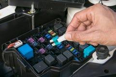 Automechaniker, der eine Autosicherung überprüft Lizenzfreies Stockfoto