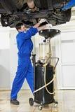 Automechaniker, der Schmieröl vom Bewegungsmotor ersetzt Lizenzfreie Stockfotos