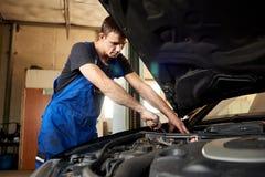 Automechaniker in der Uniform der schmutzigen Arbeit repariert Auto in der Garage Lizenzfreie Stockbilder
