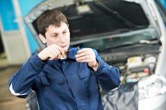 Automechaniker, der Zündkerze des Motors prüft Stockbilder