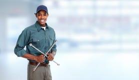 Automechaniker mit Reifenschlüssel in der Garage Lizenzfreies Stockbild