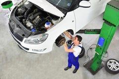 Automechaniker repariert Bremsen eines Fahrzeugs auf der anhebenden Plattform lizenzfreie stockfotografie